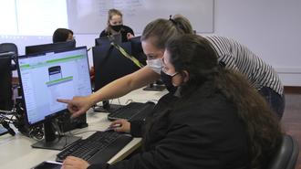 Em foto, uma pessoa está sentada, em frente a um computador. Em segundo plano, outra pessoa está em pé, apontando para a tela do computador. Ao fundo, uma pessoa em pé e um quadro branco