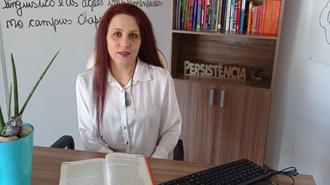 """Darlise está sentada atrás de uma mesa de escritório, a qual tem um livro aberto, um vaso com uma planta e um teclado de computador. Atrás da mestra há um quadro branco, com um texto escrito em caneta preta e uma estante com livros e um objeto decorativo esculpido com a palavra """"Persistência""""."""