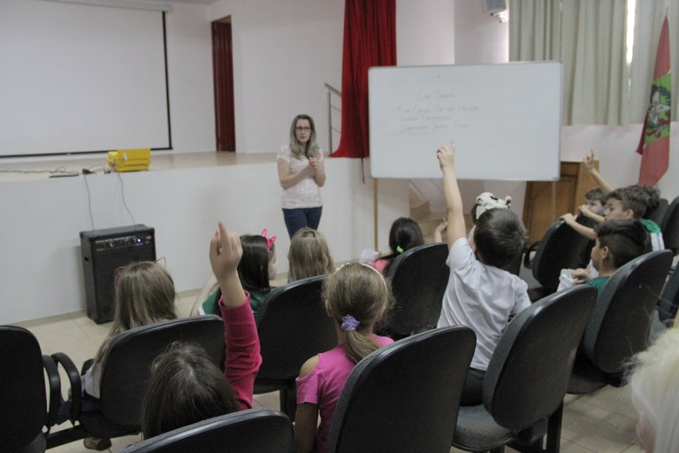 Estudantes em um auditório, de costas, olham para a professora, que explica de frente para a câmera