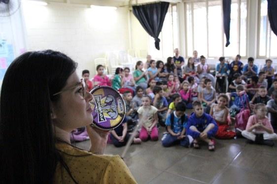 Integrante da bateria está tocando um instrumento em primeiro plano e, ao fundo as crianças estão sentadas no chão, assistindo à apresentação