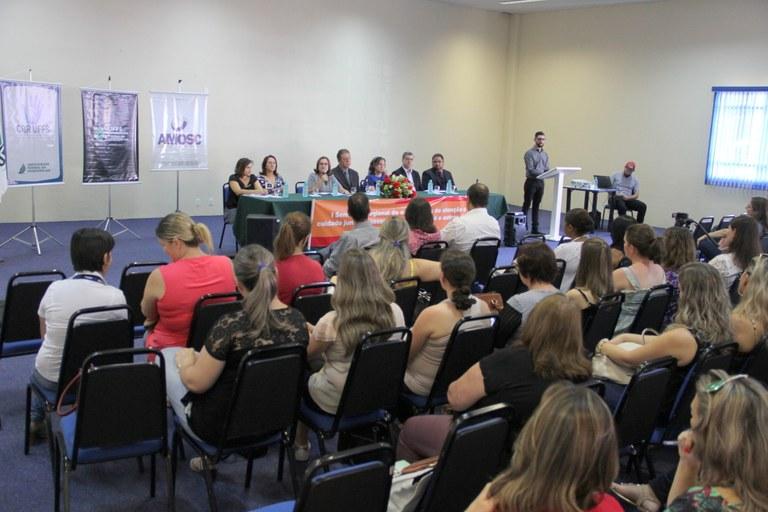 Auditório cheio, com as pessoas sentadas de frente para a mesa de honra, que é formada por sete pessoas