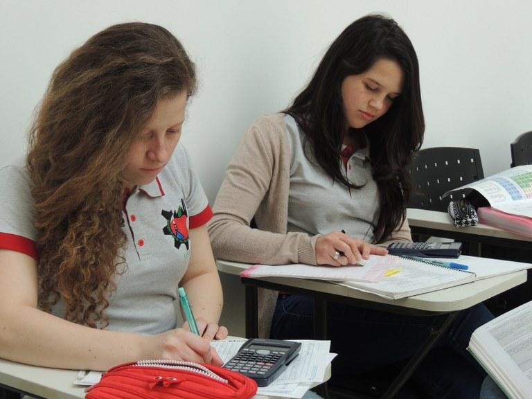Duas meninas estudantes sentadas nas cadeiras em sala de aula realizando exercícios da disciplina