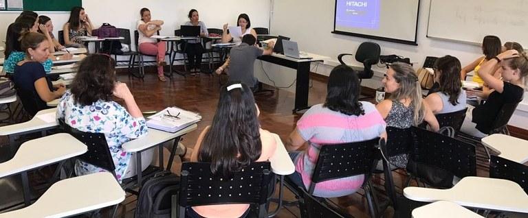 Fotografia mostra sala de aula com pessoas em reunião, sentadas em círculo
