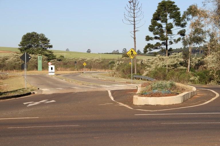 Foto mostra a entrada da UFFS - Campus Chapecó, no entroncamento com a rodovia. Há árvores ao redor, uma guarita ao centro e, na mesma direção, mas mais longe, um totem de identificação da UFFS