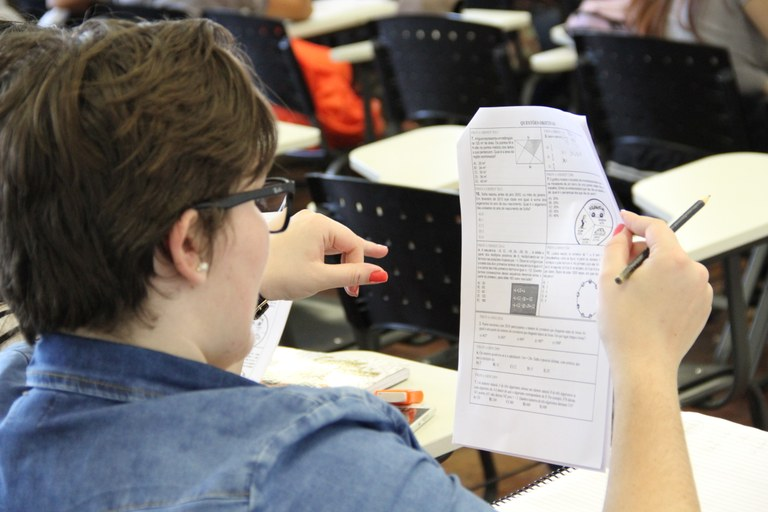 Menina lendo o material disponibilizado pela UFFS de costas para a câmera