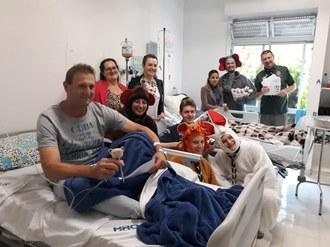 Um paciente está em um leito, e familiares e voluntários do projeto estão em pé, atrás da cama