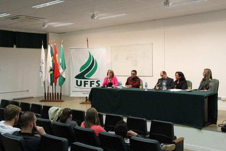 Auditório com pessoas olhando para a frente, onde mesa está composta por quatro pessoas, uma delas falando ao microfone