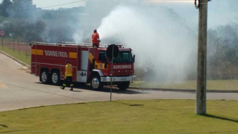 Bombeiro em cima de caminhão combate as chamas na mata com água