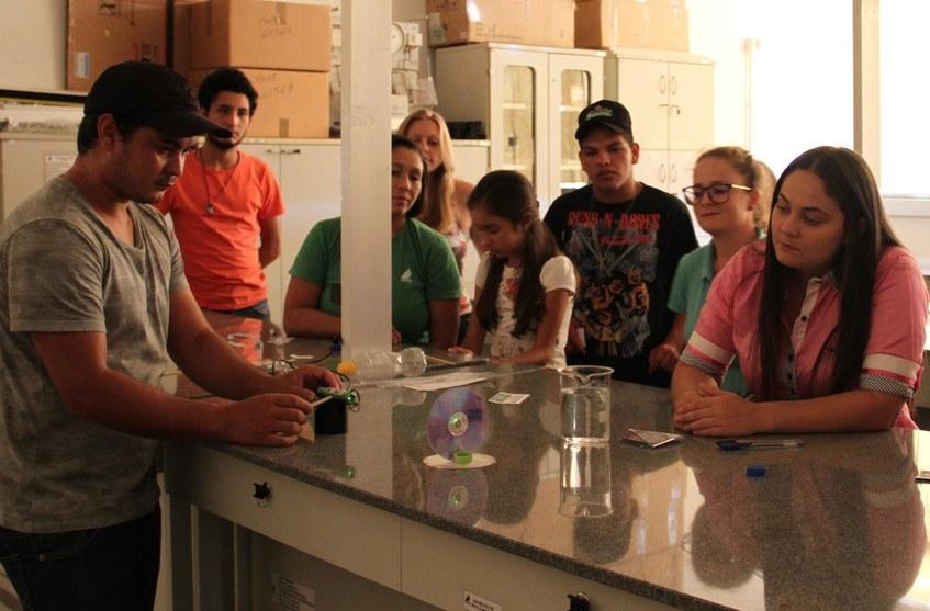 Na imagem oito estudantes estão poscionados ao lado de bancada de laboratório onde realizam experimentos.