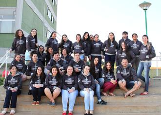 Na imagem, um grupo de acadêmicos sentados em uma escadaria, ao fundo o bloco de salas de aula.