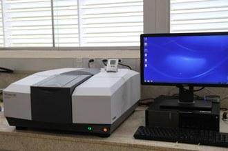 Na imagem, o espectrofotômetro está posicionado em uma bancada, ao lado de um computador.