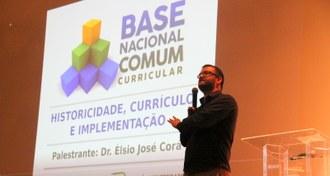 Na imagem o professor Élsio José Corá está no palco falando para o público. Ao fundo a projeção de imagem com título da palestra.