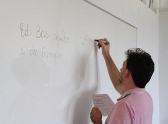Na imagem um professor está escrevendo no quadro branco e segurando uma anotação com a outra mão.
