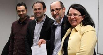 Na imagem quatro pessoas estão em pé, posando para foto. Uma delas que está ao centro segura em suas mãos documento assinado.