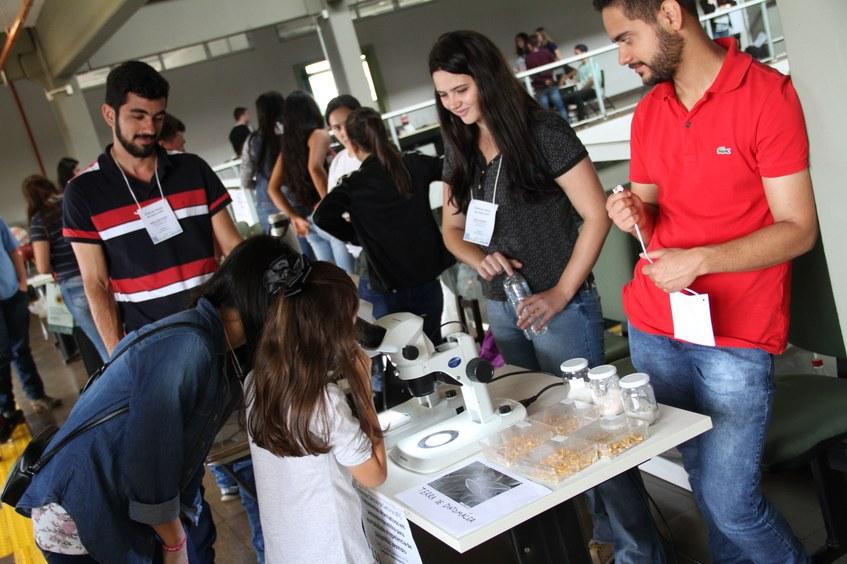 Na imagem estudante observa experimento em microscópio. Ao seu redor outros estudantes acompanham apresentação.