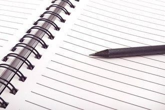 Imagem de um caderno, em plano fechado, mostrando as linhas e um lápis sobre ele