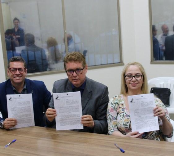 Foto em plano médio destacando os participantes sentados lado a lado e mostrando o termo do convênio