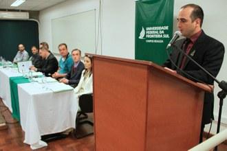 Um homem falando para o público. Ao seu lado, integrantes da mesa de honra observam.