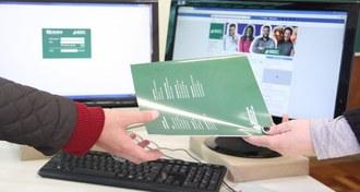 A foto, em plano de fechado, que retrata a entrega de um material publicitário da UFFS. O plano só registra as mãos das pessoas envolvidas.