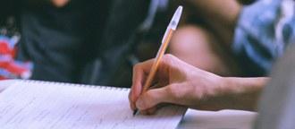 Fotografia em plano fechado - uma mão segurando um lápis escrevendo sobre um caderno