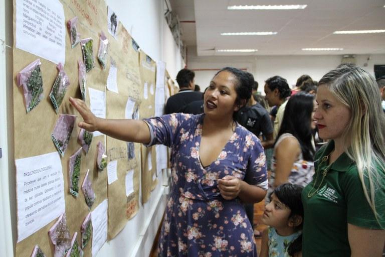 Duas alunas da UFFS observam uma exposição de plantas medicinais