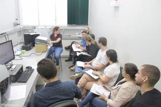 Foto em plano aberto com várias pessoas numa sala