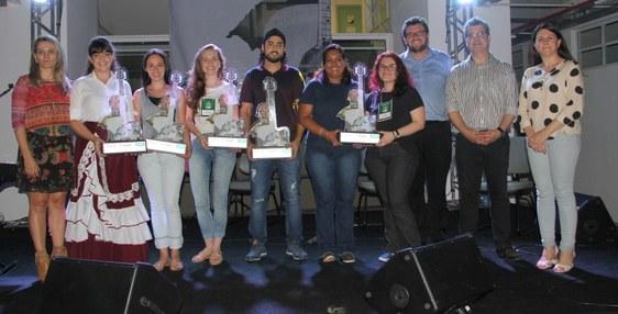 Em um palco, dez pessoas, em pé, posam para a foto oficial dos ganhadores do Festival Cultura de Fronteira. Algumas pessoas seguram o troféu do Festival.