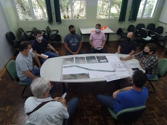 Foto aparecendo pessoas reunidas em torno de mesa