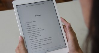 Foto em plano fechado que mostra duas mãos segurando um iPad.
