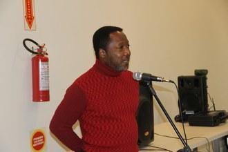 Um homem negro fala ao microfone