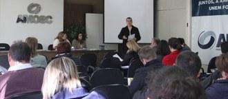Foto em plano aberto de um auditório. Pessoas sentadas observam um homem, em pé, que está falando.