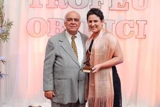 """Fotografia em médio plano de uma mulher de cabelos curtos e um homem de terno. Ela segura o troféu e sorri para a foto. Eles estão lado a lado. Atrás deles um painel escrito: """"Troféu Obirici""""."""