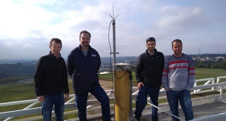 Quatro pessoas em pé, na laje do Bloco A, ao lado da estação de satélite