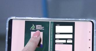 Imagem mostra, em plano fechado, as mãos de uma pessoa manipulando um smartphone. Na tela, uma carteirinha do RU