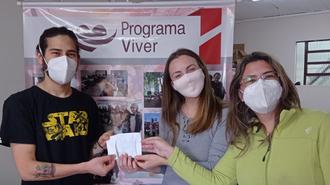 Em frente a um banner do Programa Viver, jovem presidente do CA entrega envelope a duas mulheres. De máscara, todos olham para a câmera e é possível perceber que estão sorrindo.