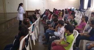 Estudante de jaleco fala, de frente para as crianças, que estão sentadas em cadeiras brancas, em uma sala