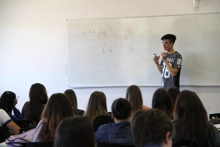 Estudante explicando resolução no quadro branco. Jovens das escolas aparecem de costas, olhando para o graduando
