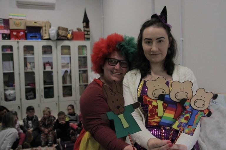 Duas estudantes fantasiadas mostram personagens colados em palitos. Crianças estão ao fundo