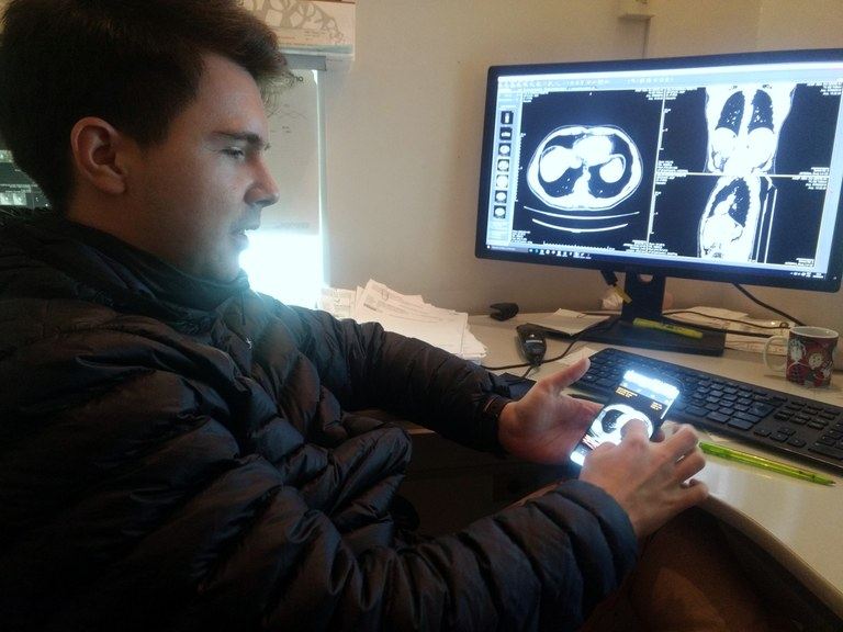 Venson está em frente a um computador, segurando um smartphone com imagens de exames