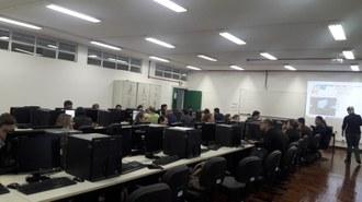 Sala com computadores dispostos em linha, e pessoas utilizando os equipamentos