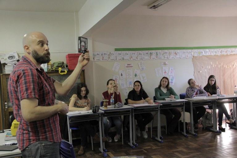 Professor, de frente para um turma disposta com mesas e cadeiras em meia lua, mostra jogo