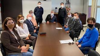 Imagem de uma sala de reuniões, onde as pessoas estão sentadas ao redor de uma mesa retangular. A disposição dos presentes está em formato de U, tendo, ao fundo, duas pessoas em pé