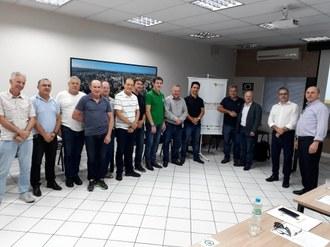 Homens em pé em uma sala, dispostos em meia-lua