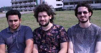 Em plano médio, os três vencedores estão olhando para a câmera, com o fundo do gramado e dos prédios da UFFS - Campus Chapecó