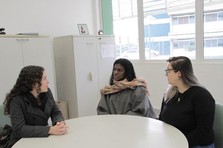 A coordenadora e as intérpretes de Libras estão sentadas ao redor de uma mesa redonda e conversando