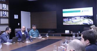 Foto em plano aberto mostra parte de uma mesa de reuniões, com pessoas sentadas ao redor, e, em frente, uma apresentação projetada na tela, com a foto da UFFS - Chapecó