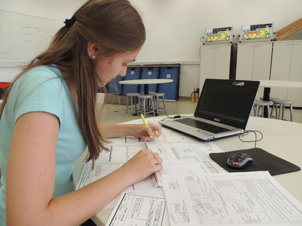 Aluna sentada em uma mesa com projeto arquitetônico e um notebook