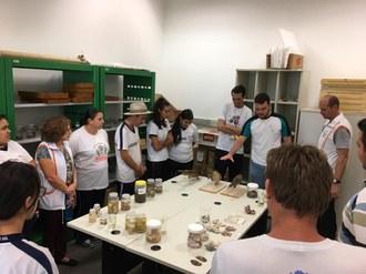 Os estudantes formam um círculo ao redor de mesas onde estão expostos materiais relacionados à Aquicultura.