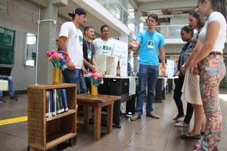 Na imagem quatro estudantes realizam a apresentação do projeto de confecção e venda de móveis e decoração a partir de materiais reciclados. Ao lado dos estudantes uma estante baixa e uma mesa de centro feita de madeiras reaproveitada.