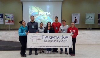 Na imagem cinco estudantes estão em pé segurando uma faixa que contém o logo da Desenvolve Consultoria Júnior e informações para contato